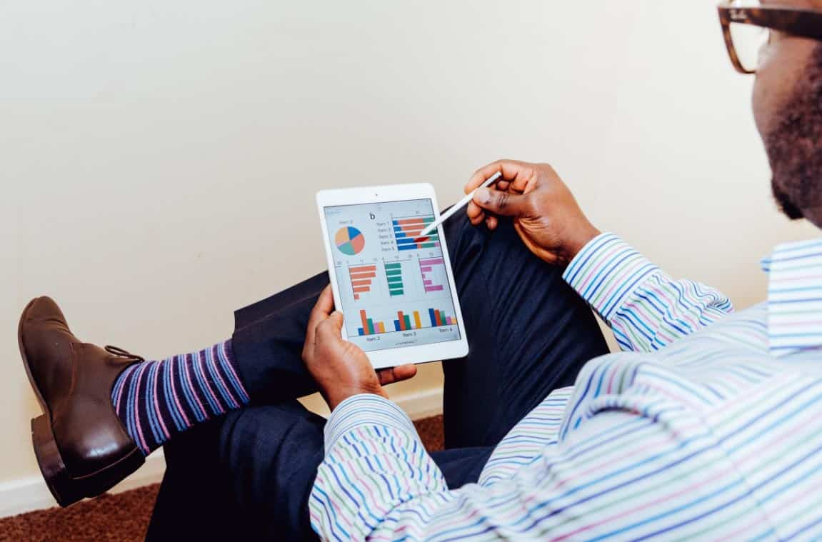 Man with glasses sitting with legs crossed with colorful socks exposed reviewing graphs and charts on tablet