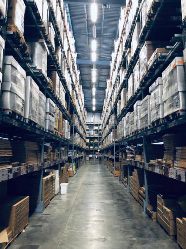 Lights running along aisle with stacked pallets in warehouse