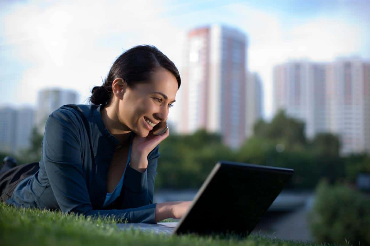 Smiling woman laying on her stomach in the grass on a laptop with a blurry city skyline in the distance