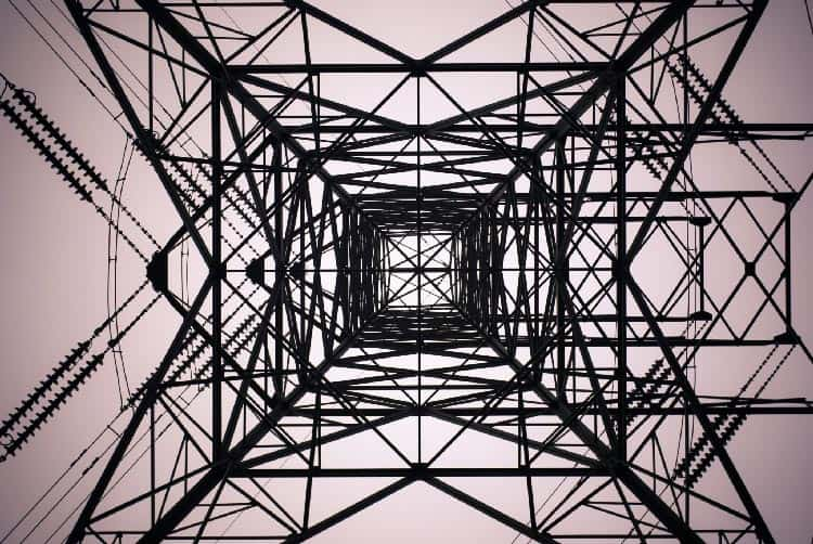 Ground view from inside of a cell tower looking up at the structure into the dusk sky