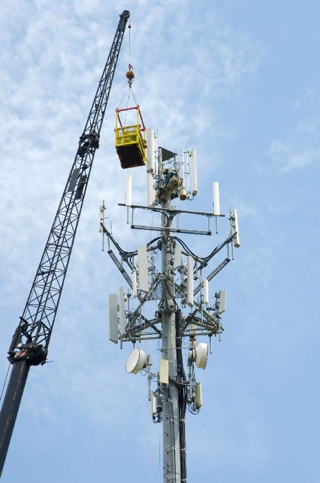 Tall crane holding a yellow crane basket next to a cell tower in front of a blue sky