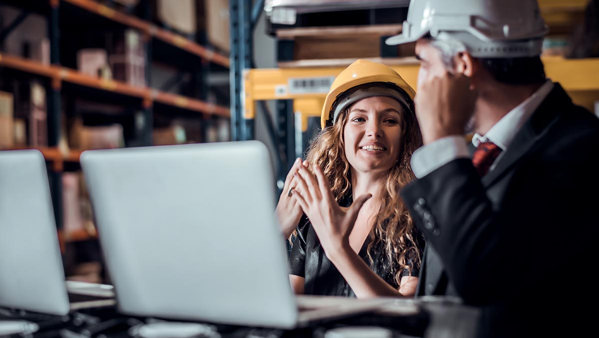 Woman wearing a hard-hat in a warehouse talking with the building facility manager