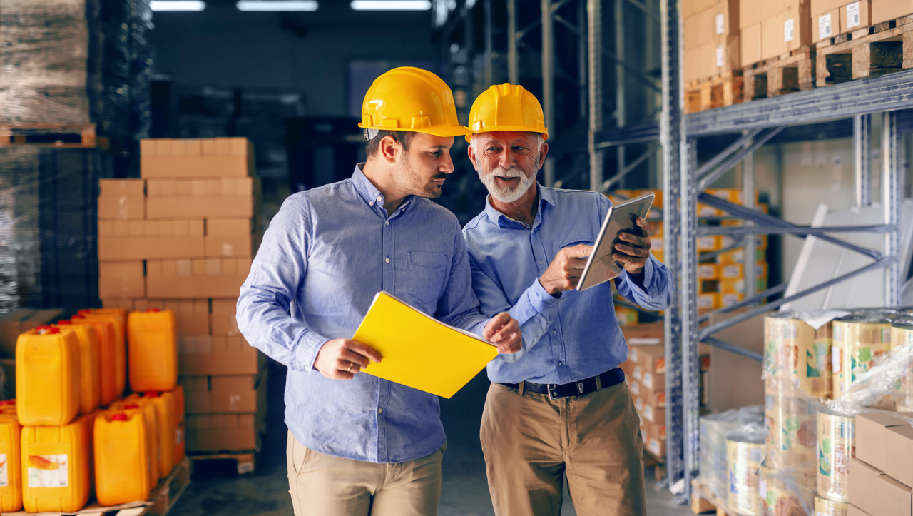 Two men in a building warehouse reviewing data